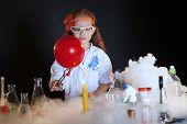 Image of cute little schoolgirl watching reagents