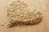 foto of staples  - Heap of uncooked oats on a wooden chopping board arranged in the shape of a heart.