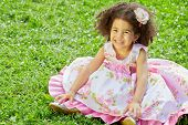 Little mulatto girl sits on grassy lawn spreading hem of her dress on sunny day