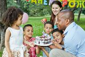 Family of six looks at birthday cake with burning candle on it, happy birthday sign behind theirs ba