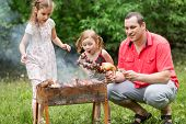 A family of three making barbecue on the grill on nature, little girl blowing on a skewer with mushr