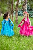Two little girls in beautiful puffy gowns perform on grassy lawn between trees in park