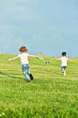 Little girl and boy run on meadow to fly kite, rear view, focus on girl