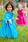 Two little girls in puffy gowns perform on grassy lawn in park, mulatto girl in focus