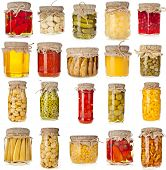 Collection set of many homemade glass bottles with preserved food close up isolated on white backgro