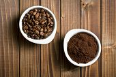 stock photo of coffee grounds  - top view of coffee beans and ground coffee in bowls on wooden table - JPG