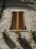 foto of assis  - 3 Flower pots hanging below a window in Assis Italy - JPG