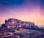Vintage retro hipster style travel image of Mehrangarh Fort in twilight on sunset, Jodhpur, Rajasthan, India  with grunge texture overlaid