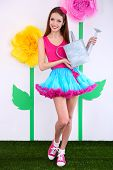 Beautiful young woman in petty skirt holding watering can on decorative background