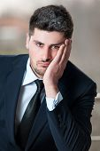 stock photo of insulting  - Portrait of a sad businessman in black suit and stress, problem, crisis concept - stressed