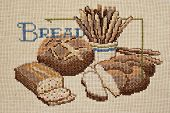 Finished cross stitch design of bread still life (worked on homespun aida cloth)