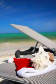 Santa Hat And Seashell On Chaise Longue On Beach