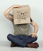 pic of incognito  - Man with cardboard box on his head sitting on floor near wall - JPG