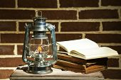 picture of kerosene lamp  - Burning kerosene lamp and books on brick wall background - JPG