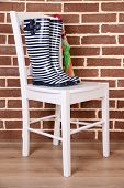 Pair of colorful gumboots on chair on color wall background