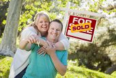 Happy Couple Holding House Keys In Front of Sold Real Estate Sign.