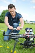 Young engineer crouching while fixing propeller of UAV drone in park