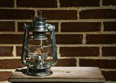 Burning kerosene lamp on brick wall background
