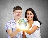 Young happy couple holding earth planet in palms. Elements of this image are furnished by NASA