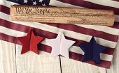 A rolled up US Constitution on an American Flag with red white and blue stars in the foreground. High angle shot on a rustic wooden table. The image has a vintage retro feel.