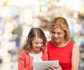 family, child and technology concept - smiling mother and daughter with tablet pc computer