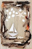 Sea shell, driftwood and seaweed abstract design with small boat over old oak background.