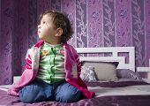 foto of 15 year old  - Cute baby one year old sit on bed at home - JPG
