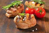 grilled pieces of pork tenderloin served with fresh herbs and tomatoes