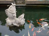 Stone Carve Of Koi Carps In Pond