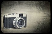 Vintage rangefinder style camera on a grunge background simulating an old film frame with space for