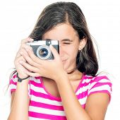 Beautiful young girl taking a picture with a vintage looking  compact camera looking through the viewfinder (isolated on white)