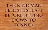 The kind man feeds his beast before sitting down to dinner - Hebrew Proverb on wooden red oak backgr