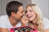 Relaxed happy young couple eating candies at home