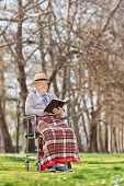 An old man reading a novel in park