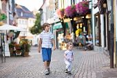 Cute School Boy And His Baby Sister Running And Playing In A Historical City Center Of German city