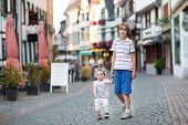 Brother And His Little Baby Sister Walking And Playing In A Historical City Center In Germany