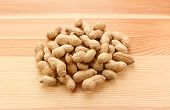foto of groundnut  - Heap of monkey nuts peanuts or groundnuts in shells on a wood grain background - JPG