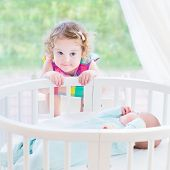Cute Toddler Girl Playing With Her Newborn Baby Brother In A Bedroom With A Big Window