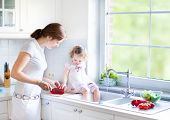Cute Toddler Girl Helping Her Mother To Cook Vegetables In A Beautiful White Kitchen