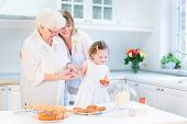 Happy Young Woman Baking A Cake With Her Senior Mother And Cute Little Toddler Daughter In A Beautif