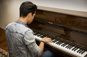 Young Handsome Male Artist Playing Classical Upright Piano
