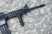 picture of m4  - M4 carbine with blank dog tags on camouflage uniform - JPG