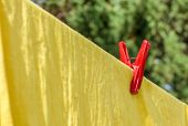 The Red Plastic Clothespin Is On The Clothesline With Yellow Cotton Cloth.