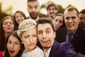 stock photo of love making  - Young couple of newlyweds with group of their firends taking selfie and making funny grimaces - JPG