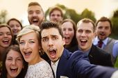 image of love making  - Young couple of newlyweds with group of their firends taking selfie and making funny grimaces - JPG