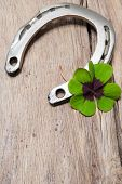 Horseshoe With A Shamrock On Old Wooden