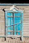 Aged wood window painted in blue colour