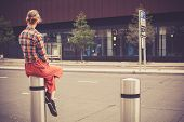 pic of bollard  - A young woman is sitting on a bollard by the roadside in the city - JPG