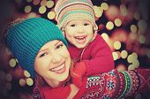 image of cheers  - happy family mother and baby little daughter playing in the winter for the Christmas holidays - JPG