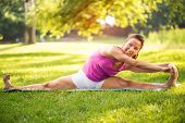 stock photo of do splits  - Beautiful young woman doing relaxing and stretching exercises in the park.